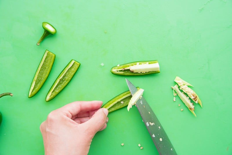 A knife removes the membrane and seeds from the jalapeno peppers