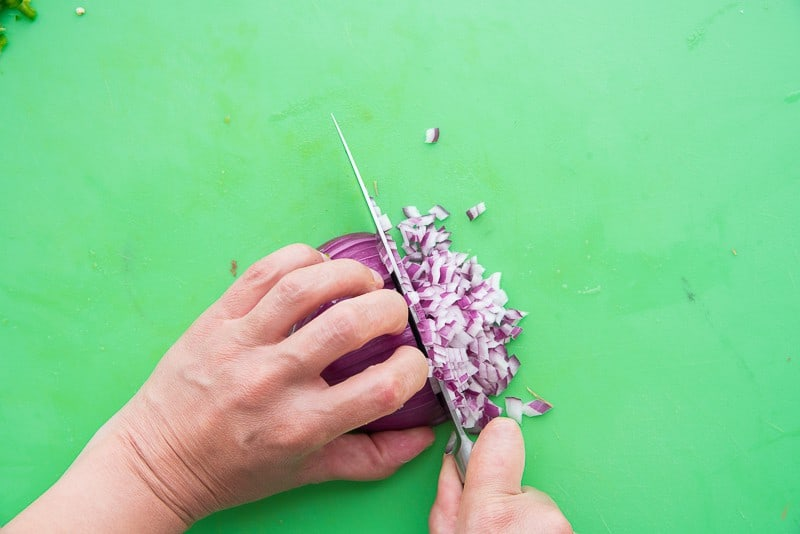 A hand uses a knife to dice a red onion