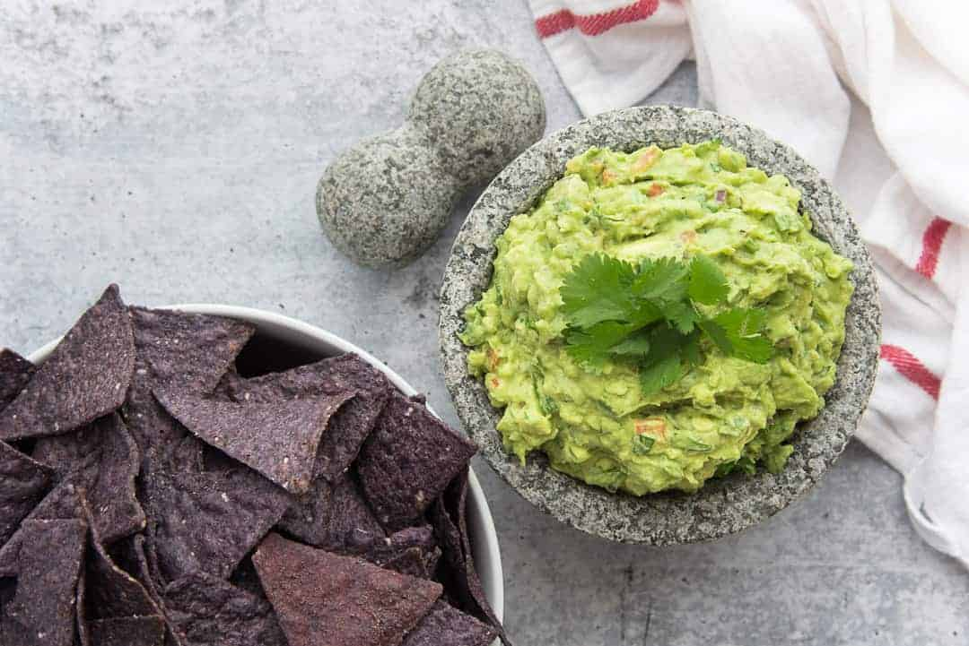 A horizontal image of a bowl of guacamole next to a bowlful of chips
