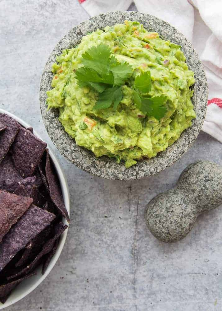 A portrait image of a molcajete filled with Guacamole