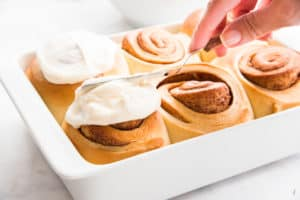 A hand spreads Cream Cheese Icing over a Cinnamon Roll that's in a white casserole dish