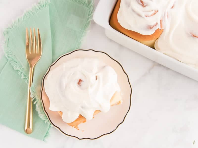 An overhead image of a Cinnamon Roll on a white plate next to a green napkin