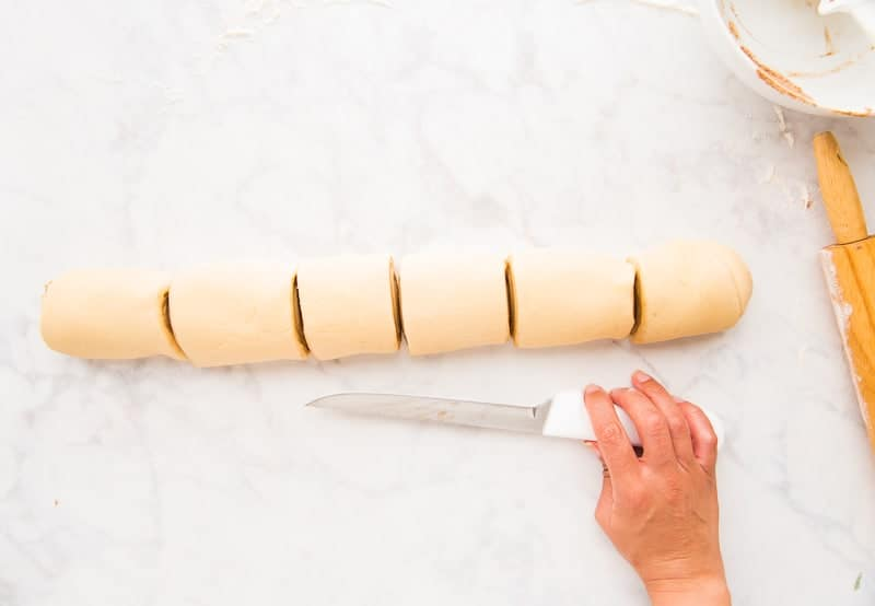 A roll of Cinnamon dough is cut into 6 portions