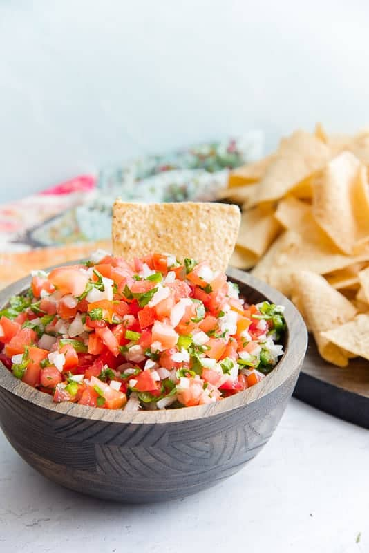 A tortilla chip sticking out of a wooden bowl filled with pico de gallo