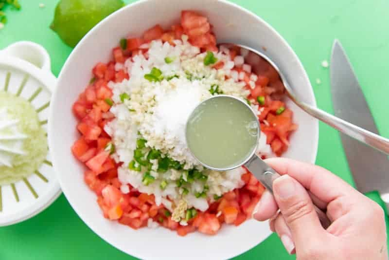 Lime juice is added to a white bowl filled with pico de gallo