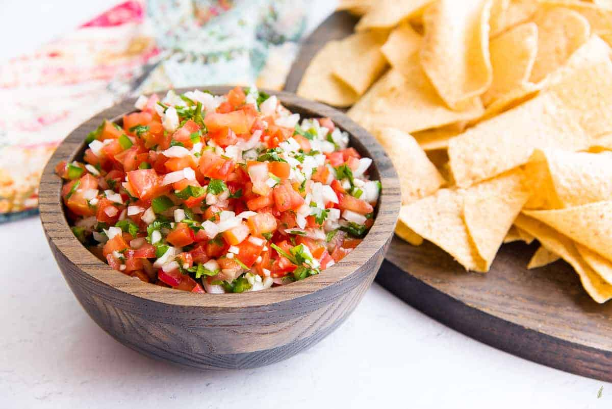 A sideview image of a wooden bowl filled with pico de gallo