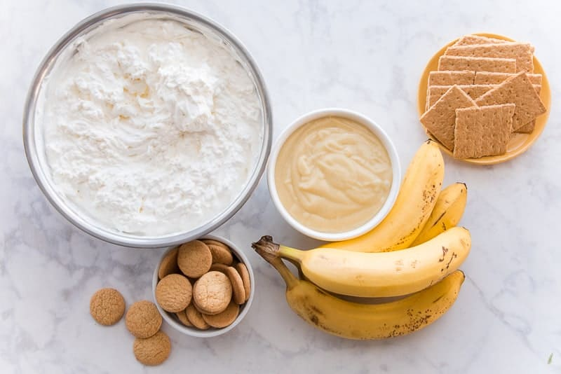 The ingredients needed to make Homemade Banana Pudding (top left to right): a metal bowl of whipped cream, a white bowl of pastry cream, a yellow plate with graham crackers on top. Bottom row: a white bowl with vanilla wafers, a bunch of yellow bananas
