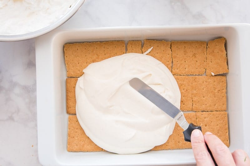 A hand uses a metal spatula to spread pastry cream over a layer of graham crackers in a white casserole dish. A metal bowl with whipped cream in it sits at top left