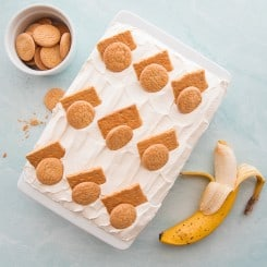 An overhead image of the Homemade Banana Pudding. In a white ceramic baking dish and garnished with graham cracker pieces and vanilla wafers. A partially peeled banana sits at bottom right. A white bowl filled with vanilla wafers is in the top left corner.