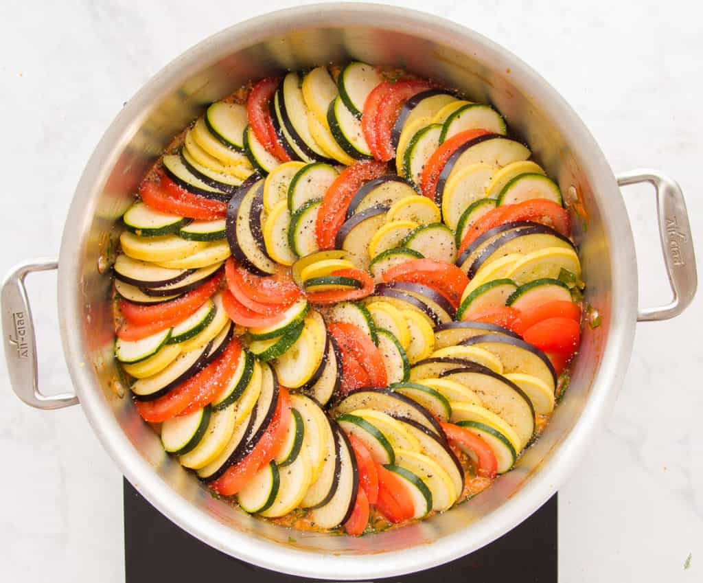 An overhead image of a round pan filled with Italian Ratatouille prior to its being baked