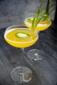 A long image of two Pineapple Jalapeno Margaritas in long stem coupe glasses