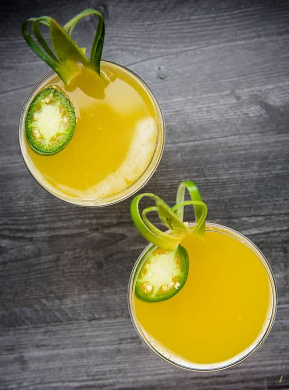 A portrait image of two glasses filled with Pineapple-Jalapeno Margaritas