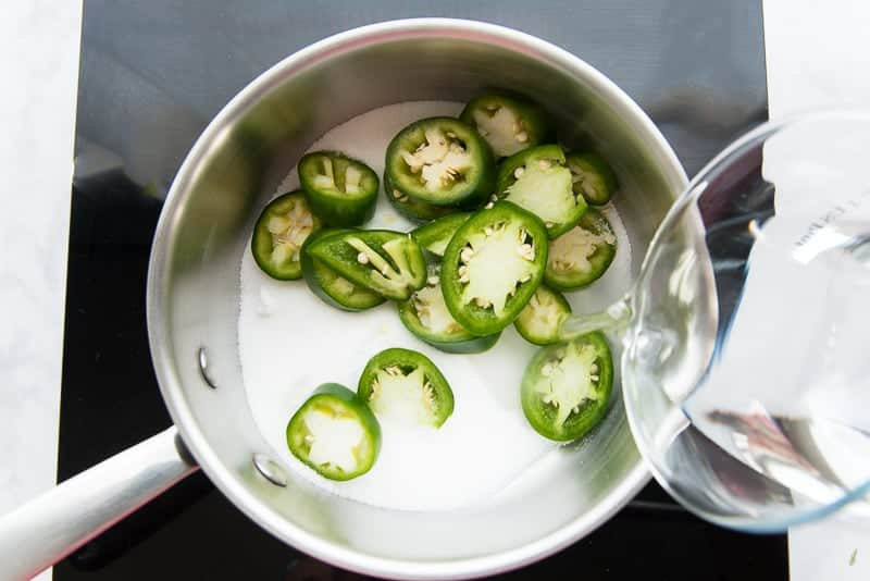 Water is poured into a saucepan filled with jalapeno slices and sugar