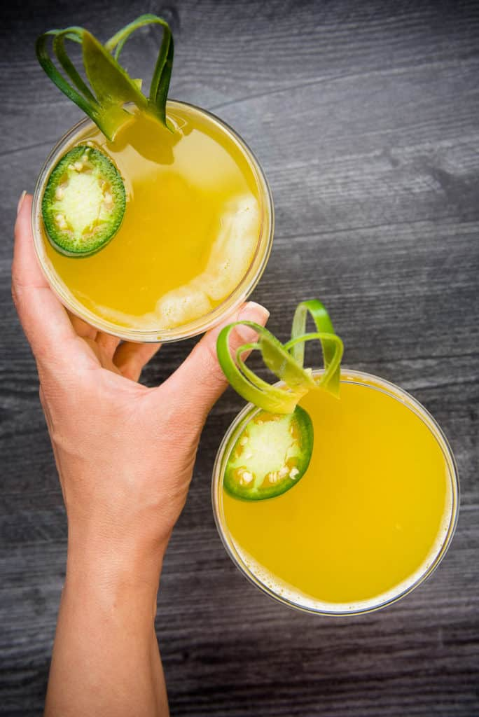 A hand holds one glass of Pineapple-Jalapeno Margarita
