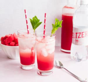 Two tall glasses filled with Watermelon Italian Soda. Mint leaves and red and white straws in each glass. A bowl of watermelon and two bottles in background