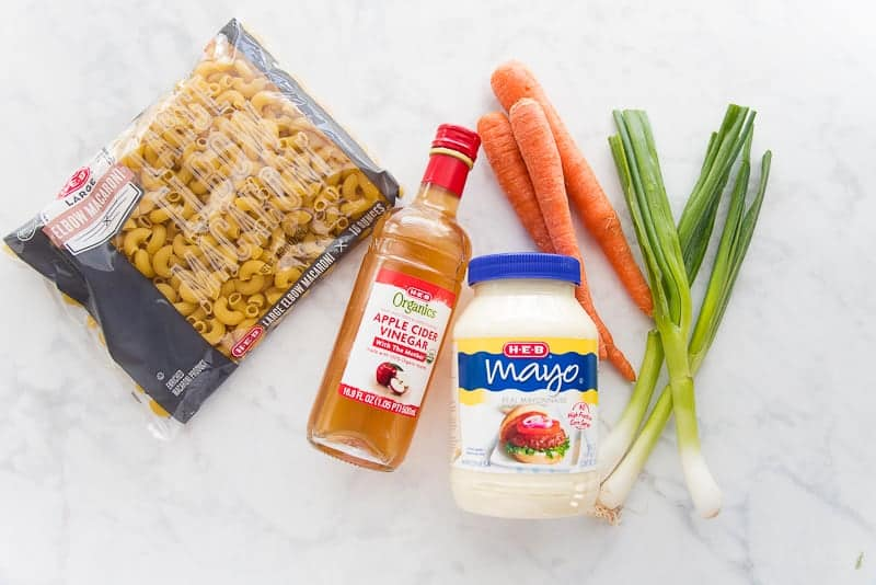 The ingredients needed for Macaroni Salad: large elbow macaroni, apple cider vinegar, mayonnaise, carrots, and green onions.