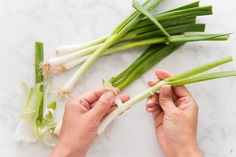 A hand peels the outer skins from green onions.