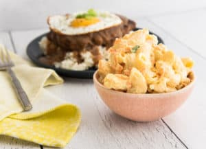 A small pink bowl is filled with Macaroni Salad. To the left of the bowl is a furled yellow napkin and a silver fork. In the background is a blue plate with rice and loco moco