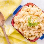 Overhead shot of blue dish filled with Macaroni Salad on right of image. Left is a furled yellow napkin on which lays a wooden spoon