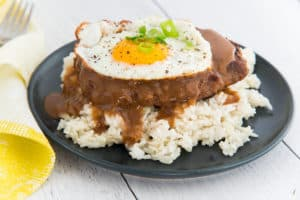 A close up image of a blue plate with white rice, loco moco, and a fried egg on it. A corner of a yellow napkin is in the left corner and fork peeks out from upper left corner