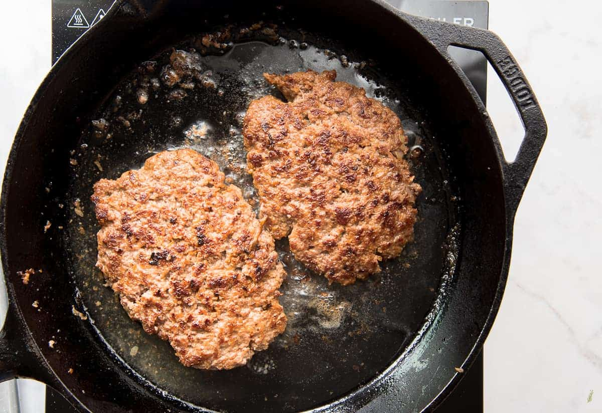 Two loco moco patties are finished browning in a cast iron skillet