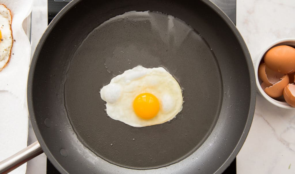 An egg is fried in a pan. To the right is a bowl of cracked shells.