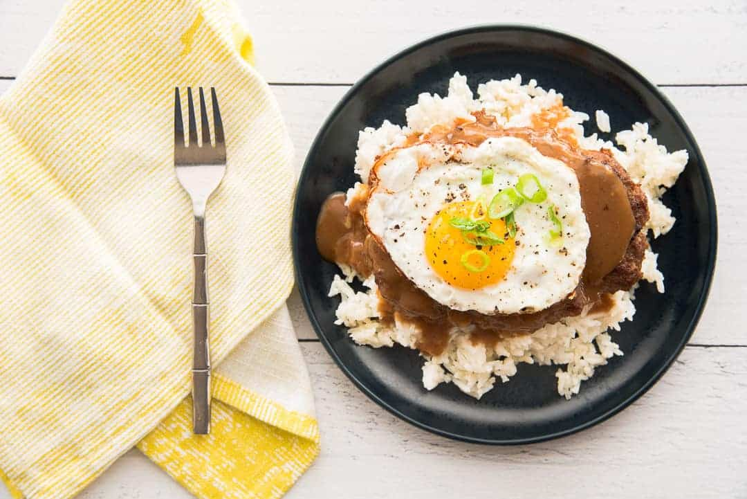 A horizontal image of a blue plate topped with loco moco, rice, and a fried egg. Left of plate is a yellow napkin with a silver fork on it.
