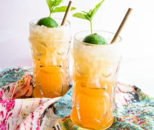 Two tiki glasses filled with Mai Tai cocktails are on a multi-colored towel in front of a pink background. A bamboo straw and lime and mint sprig are in both glasses.