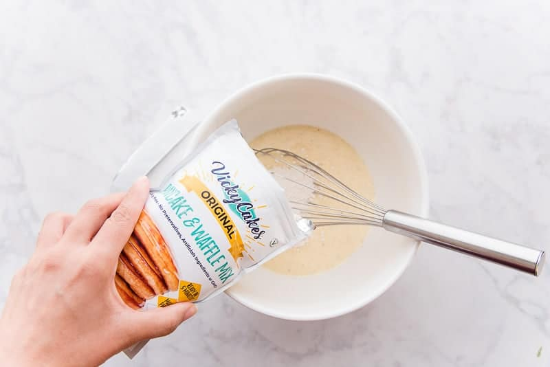 Pancake mix is added to the liquid ingredients in a white mixing bowl and a stainless steel whisk