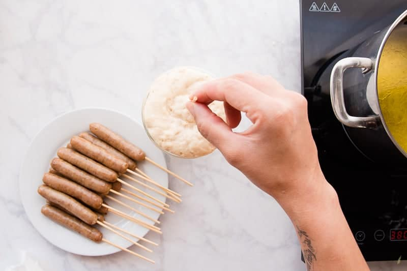 A hand dips a sausage on a stick into the pancake batter which is in a tall glass. To the left is a white plate with sausages on sticks. On the right is a silver pot filled with frying oil
