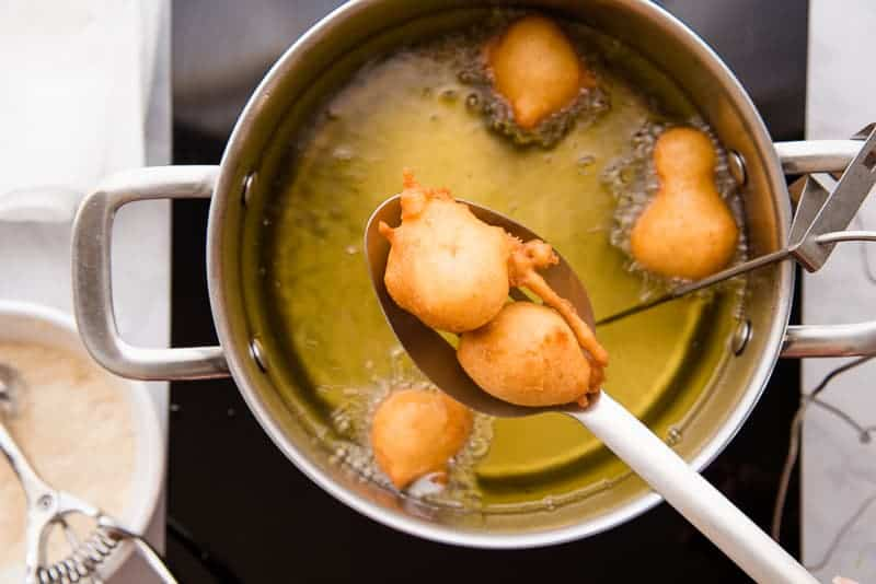The leftover dough was used to make donut balls which are being removed from the frying oil with a slotted spoon.