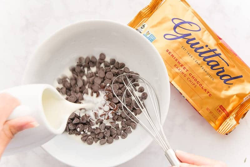 Heavy cream is poured from a white pitcher over chocolate chips in a white bowl. A gold bag of chocolate chips sits in the upper right corner