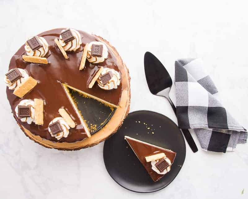 An overhead image of the s'mores Cheesecake with a slice removed and to the bottom right. A white a black plaid napkin sits to the right with a black spatula.