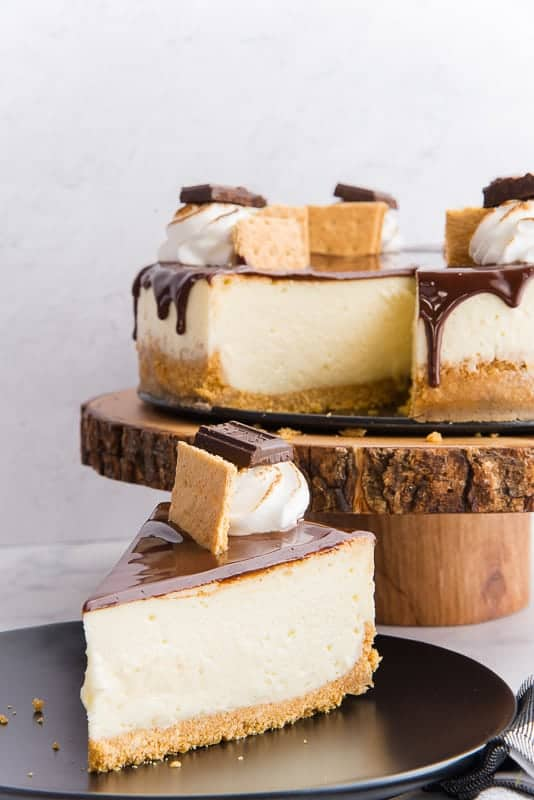 A portrait view of a slice of s'mores Cheesecake on a black plate. A wooden cake stand has the rest of the cheesecake on it in the background
