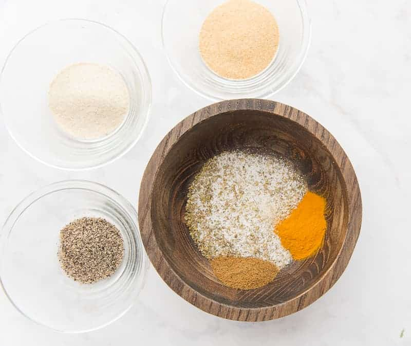 Cumin and turmeric are added to the salt and oregano in the wooden bowl. Glass bowls of pepper, onion, and garlic powder are around the bowl