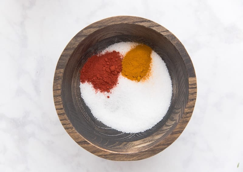 The annatto and turmeric are added to the salt in the dark wooden bowl