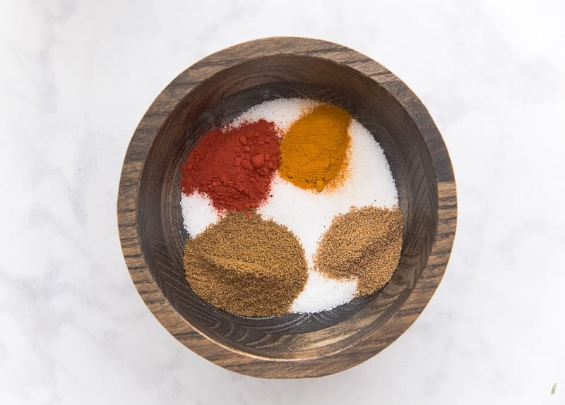 The cumin and coriander are added to the other spices in a dark wooden bowl