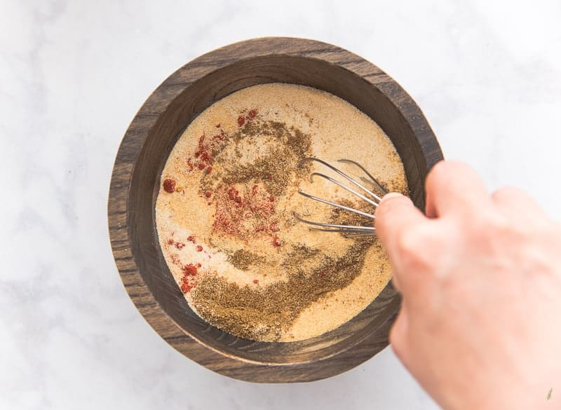 A hand combines the spice blend in the wooden bowl using a whisk
