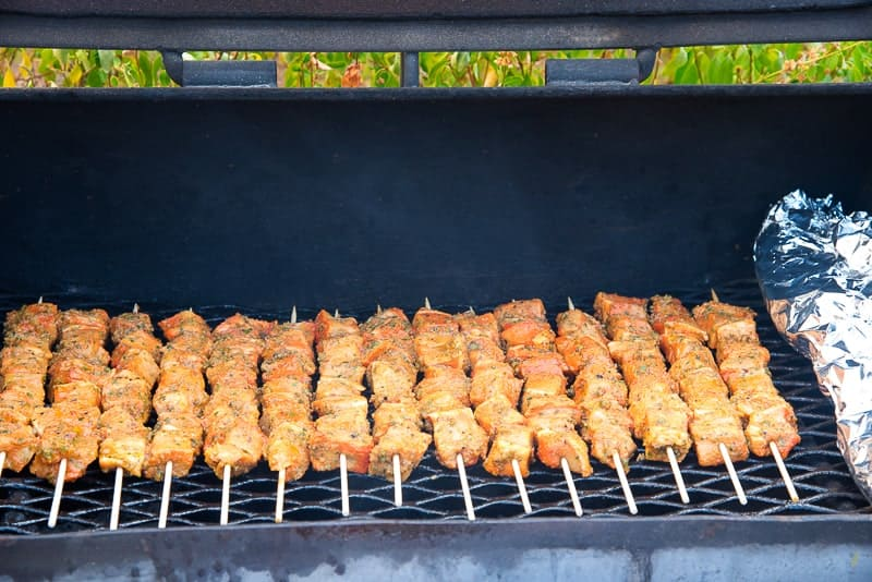 Pinchos are on arranged on the black grill.