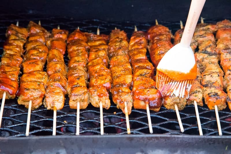 A white brush is used to brush sauce on the Pinchos on a black grill