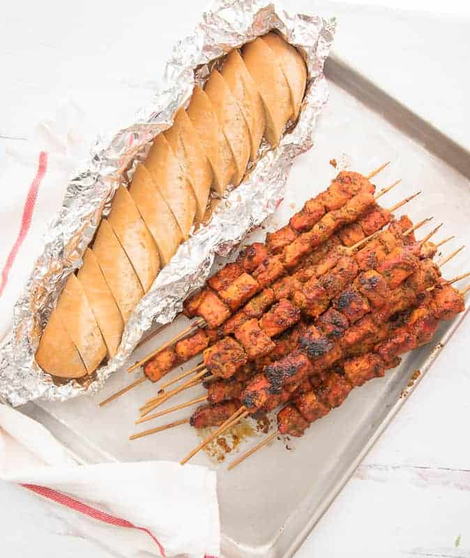 A long image of a sheetpan of Pinchos next to aluminum wrapped sliced bread. White towel with red stripe to the bottom left.