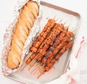 A portrait image of a stack of Pinchos on a sheetpan next to a loaf of sliced bread in aluminum foil.