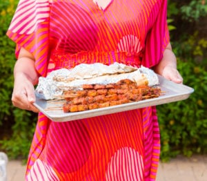 A person in a brightly colored caftan holds a sheetpan of Pinchos in front of greenery.
