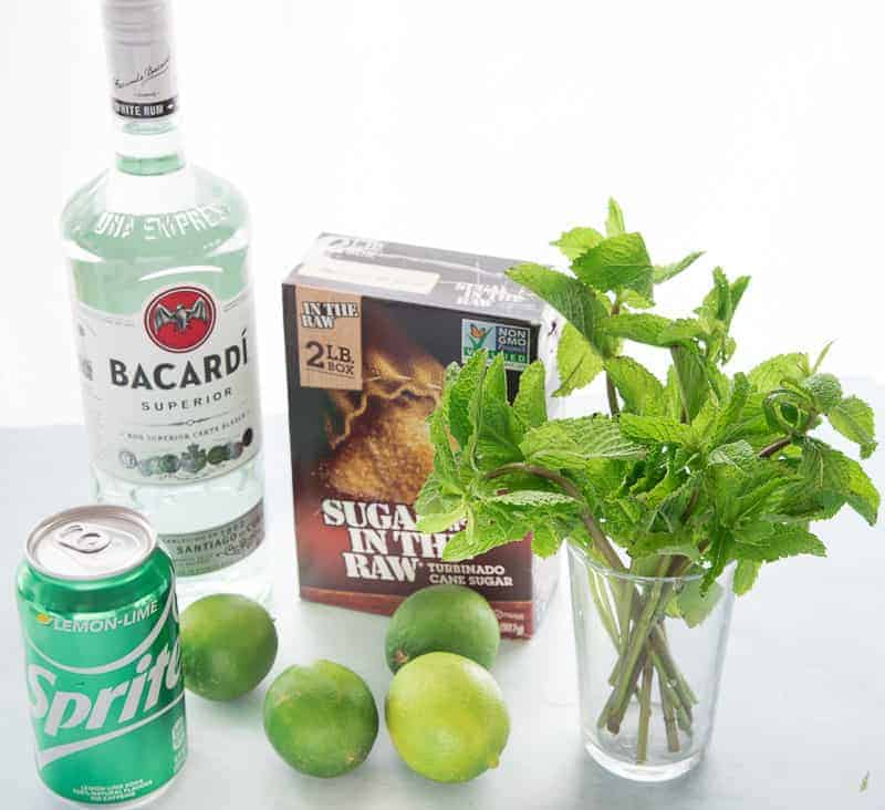 The ingredients for Puerto Rican Mojitos: white rum, turbinado sugar, mint, limes, and lemon-lime soda