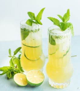 Two highballs of Puerto Rican Mojitos, sliced limes and mint sprigs lie around the glasses