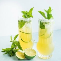 A horizontal image of Puerto Rican style Mojitos surrounded by cut limes and mint leaves.