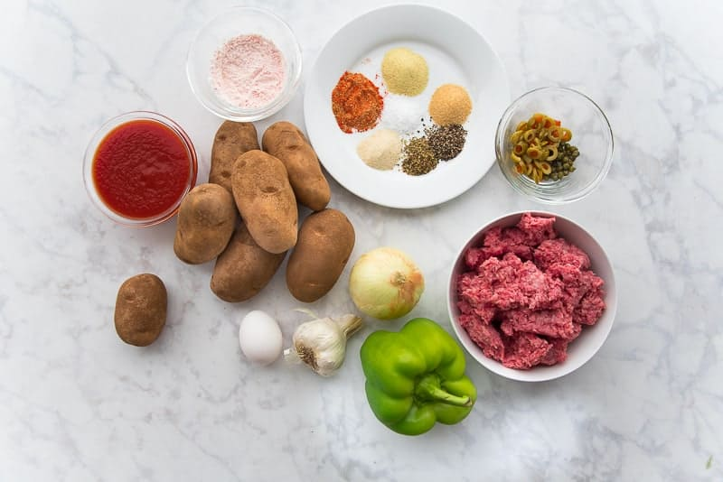 A glass bowl of tomato sauce, one of cornstarch, a plate with spices, a bowl of sliced olive and capers, a bowl of ground beef, onion, green bell pepper, garlic, egg, and potatoes
