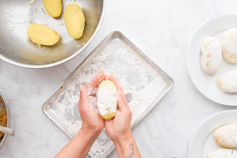 Hands hold a relleno de papa covered in cornstarch over a sheetpan filled with more cornstarch. Metal bowl in the top left holds 3 rellenos, two white plates hold more