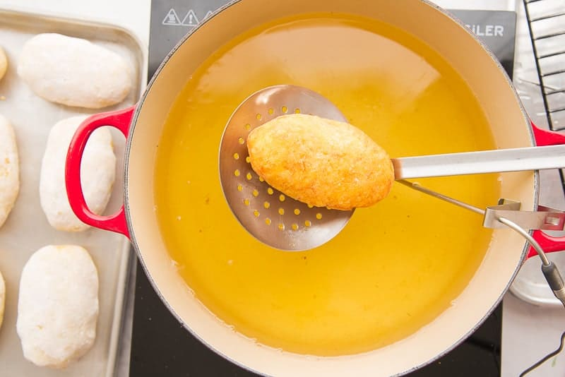 Metal spatula lifting a relleno from a red pot filled with hot oil. Sheetpan of unfried rellenos de papa on left.
