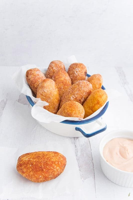 A white pan with a blue rim and handles is filled with rellenos de papa. One relleno is on a white wax paper square next to a white bowl filled with pink sauce
